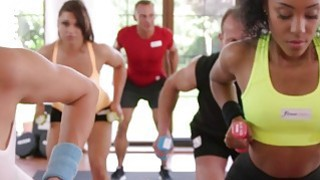 Ebony lesbian babe rubs brunette babe in gym